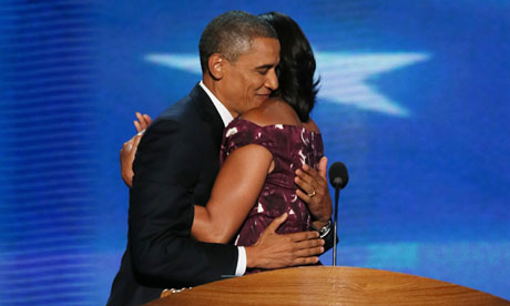 President Obama hugs 1st lady Michelle on stage at the DNC.