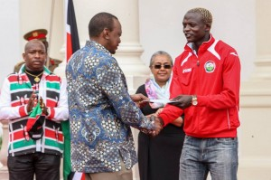 President Uhuru handing a cheque to one of the sponsored players.